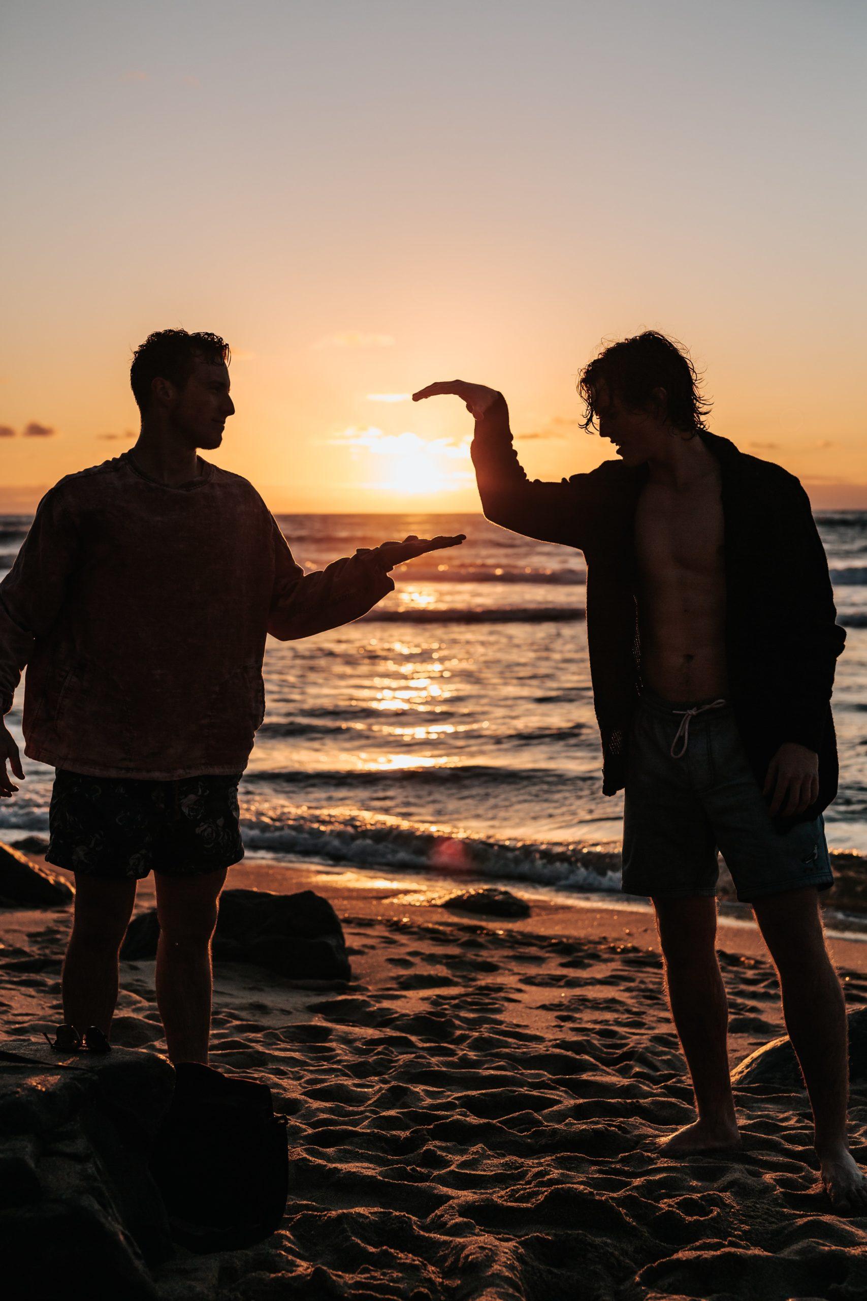 two-men-hi-fiving-on-shore